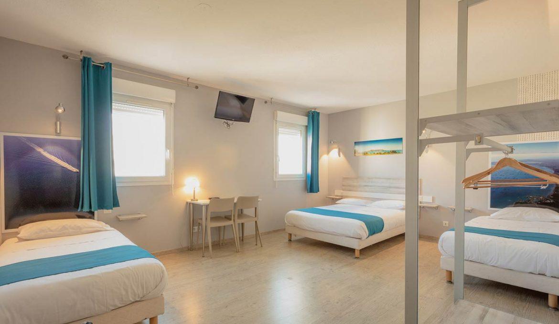 Lit double et salon d'une chambre familiale de l'Hôtel Grand Cap en Agde